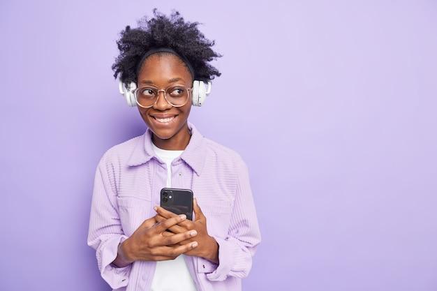 그녀의 재생 목록에 휴대 전화 다운로드 노래를 보유 하는 여자는 보라색에 고립 된 무선 헤드폰 큰 안경 유행 재킷을 착용