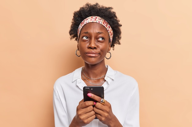 Woman holds mobile phone ponders how to answer question under post on website remembers name of product before browsing internet dressed in stylish clothes beige