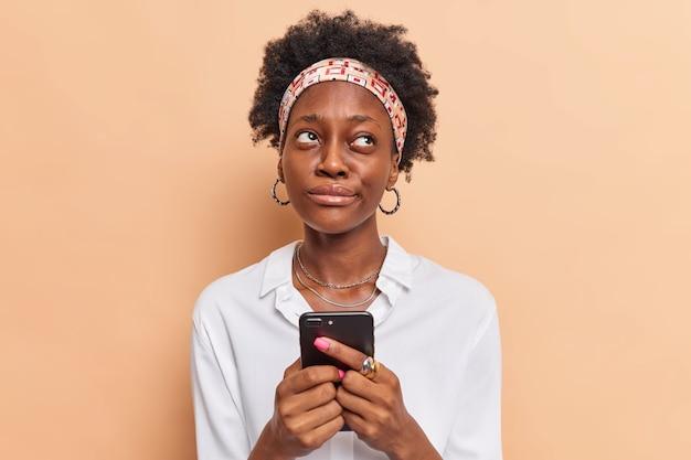 Женщина держит мобильный телефон, размышляет, как ответить на вопрос под постом на сайте, запоминает название продукта перед просмотром интернета, одетая в стильную одежду бежевого цвета