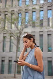 Woman holds mobile phone reads notification about transaction surfs internet wears sunglasses casual t shirt strolls in city with modern technologies messages on summer day