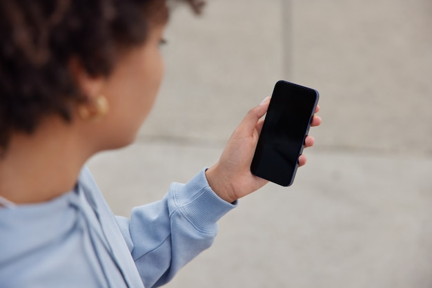 La donna tiene il telefono cellulare con lo schermo dello spazio di copia per il tuo messaggio di testo o il contenuto informativo utilizza l'app cellulare per lo shopping online indossa la felpa posa all'aperto