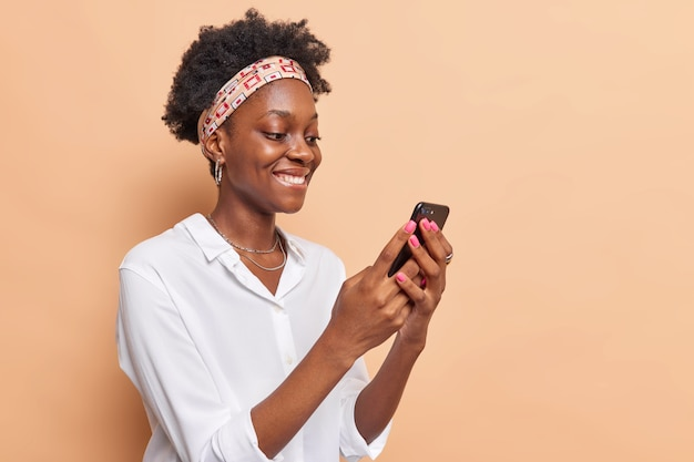 Woman holds modern mobile phone surfs net checks newsfeed in social networks wears headband white shirt isolated on beige