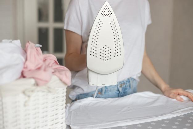Женщина держит утюг в современном стиле с антипригарным покрытием во время глажки.