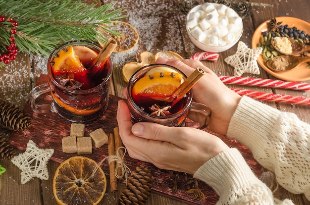 A woman holds a mug of mulled wine with an orange slice on a wooden background. dark style