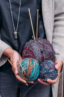 女性は編み物のために羊毛糸のマルチカラーの明るいボールを持っています。ニット糸、編み針、かせ。編み物のための美しい色。手作りのクリエイティブな編み物のコンセプト。