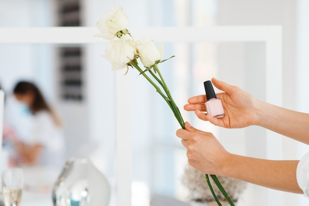 Woman holds nail varnish and flowers, beauty salon, manicure and pedicure procedure.