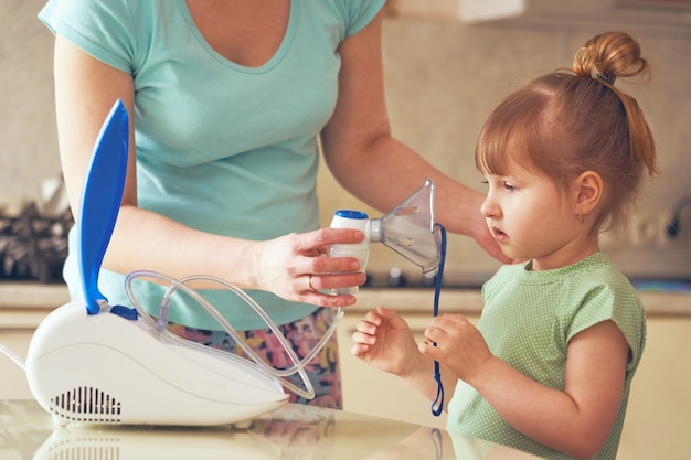 A woman holds a nebulizer mask to the little girl's face.