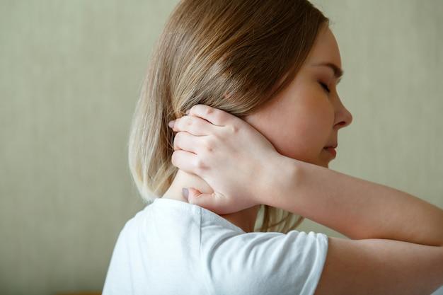 Женщина держит шею рукой при спазме шейных мышц. боль в шее, шейные позвонки, заболевание опорно-двигательного аппарата у молодой женщины.