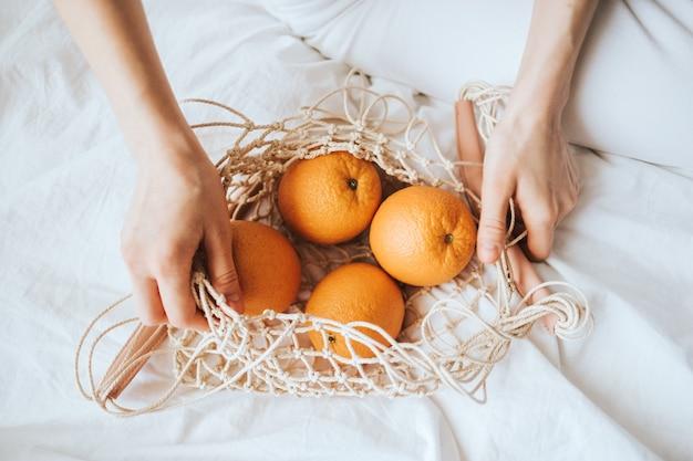 Женщина держит чистый мешок со свежими апельсинами