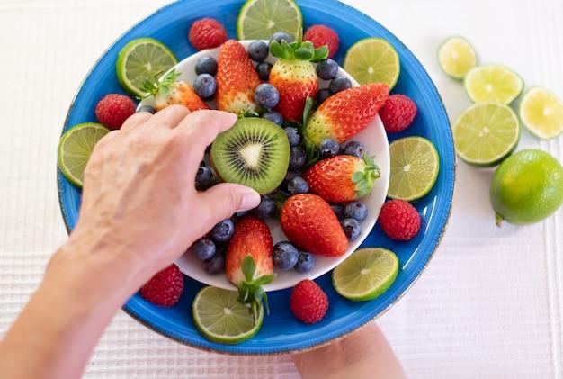 女性は、半分のキウイでイチゴとブルーベリーでいっぱいの青い皿を手に持っています。健康的な栄養と食事の概念。白色の背景