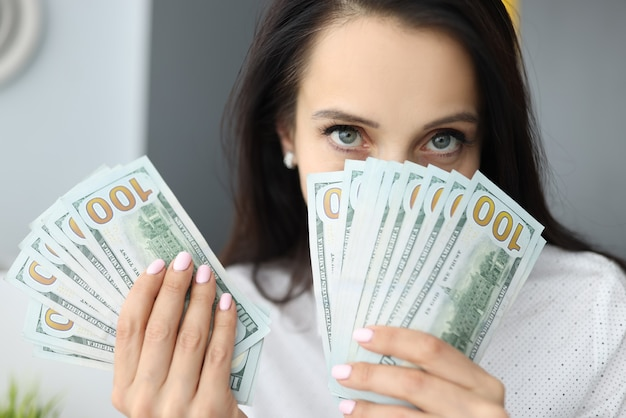 Woman holds one hundred dollar bills at face level