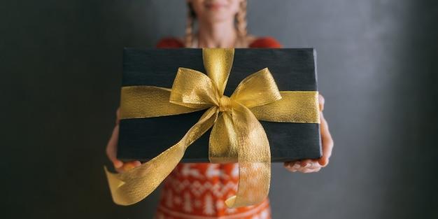 Женщина протягивает руку с подарочной коробкой и дарит подарок