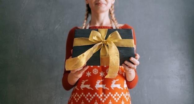 女性はギフトボックスで手を差し出し、ギフトを贈ります