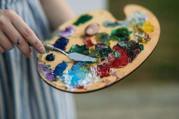 Женщина держит палитру с красками и шпателем