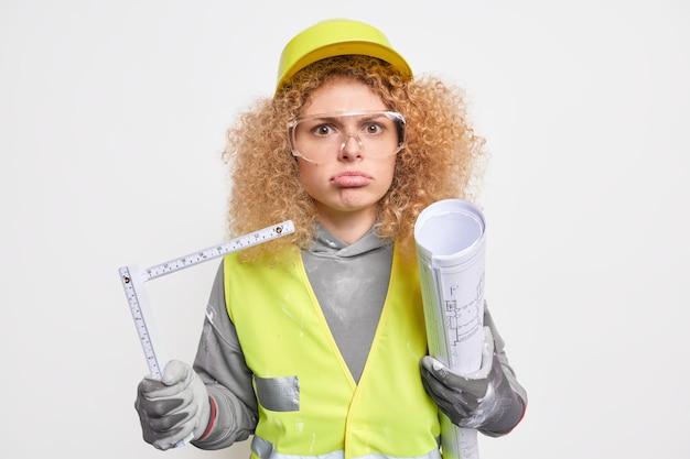 여자는 종이 청사진과 줄자를 들고 집 재건축을 하느라 바쁘다 건축 계획을 준비하고 헬멧 유니폼을 입는다