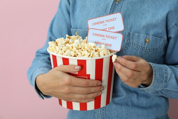 Woman holds paper cup with popcorn and tickets on pink background.