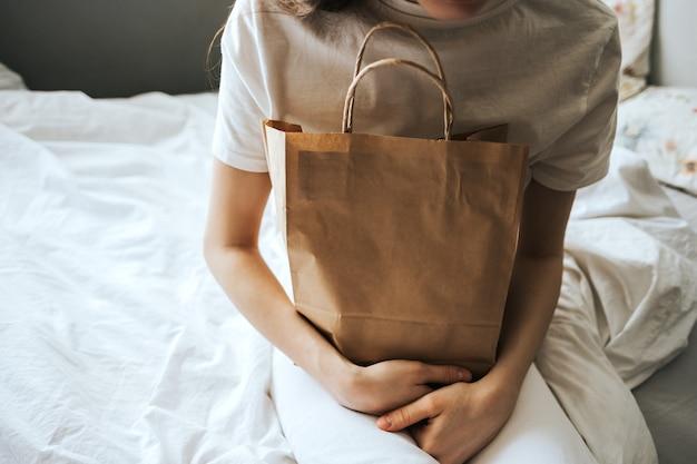 女性は手に紙のエコバッグを持っています