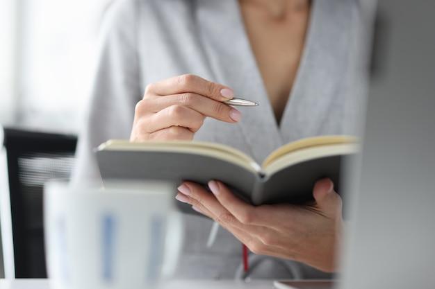 여자는 펜과 열린 일기 작업 예약 개념을 보유하고 있습니다.