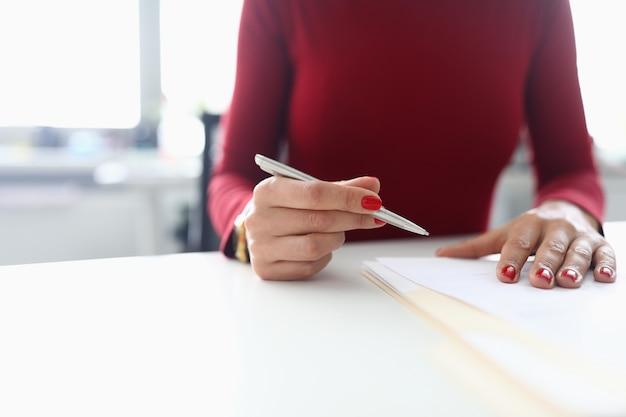 Женщина держит ручку в руках и готовится подписать документы