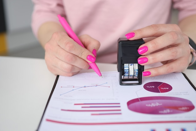 Woman holds pen and puts stamp on documents with business charts