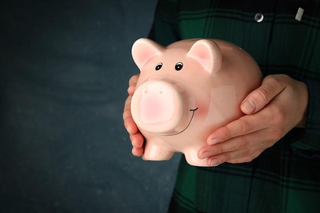 女性は暗い青色の表面に貯金箱を保持します