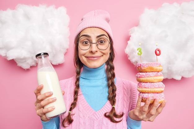 Женщина держит кучу вкусных пончиков с зажженными свечами стеклянная бутылка молока празднует свое 30-летие, одетая в повседневную одежду, изолированную на розовом