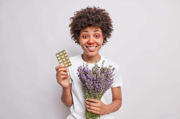 여자는 알레르기를 치료하기 위해 알약을 들고 있습니다 라벤더 꽃다발은 계절성 질병으로 고통 받고 있습니다