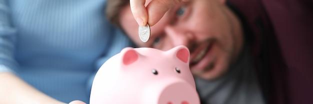 Женщина держит розовую копилку, в которую мужчина бросает монету