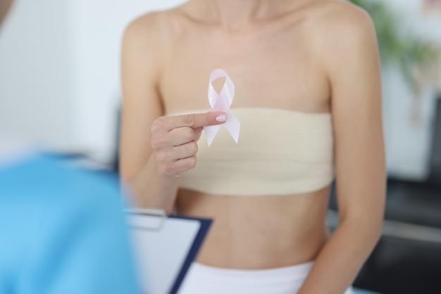 女性は、医師の予約で乳房検査中にピンクリボンを手に持っています