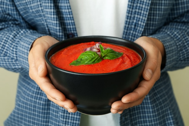 Woman holds plate of tasty gazpacho soup