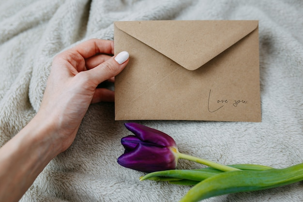 Woman holds postal envelope, envelope of craft paper and one purple tulip on beige plaid, envelope with love.
