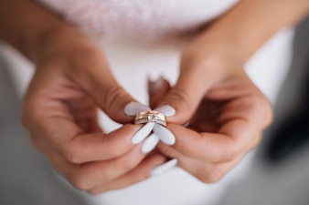 Woman holds precious wedding ring in her arms