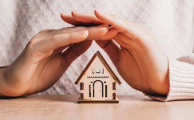 Woman holds and protects a wooden house with her hands