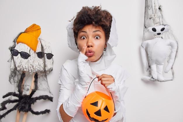 Женщина держит тыквенный трюк или угощение держит губы скрещенными носит костюм на хеллоуин позирует на белом