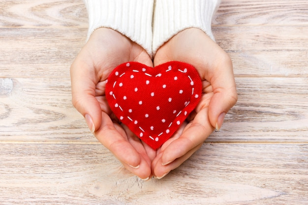 A woman holds a red heart in her hands. love concept
