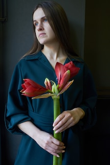 Woman holds a red hippeastrum flower