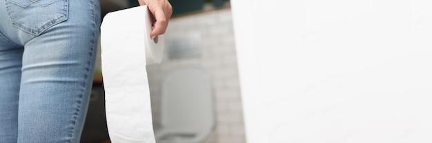 女性はトイレに行く間、手にトイレットペーパーのロールを持っています