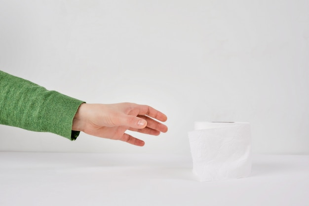 Woman holds a roll of tissue in hands on a white background. concept of covid-19 quarantine.doomsday panic people panic.
