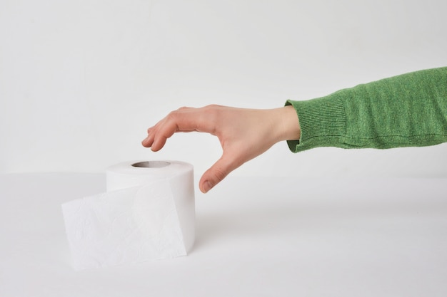Woman holds a roll of tissue in hands on a white wall.