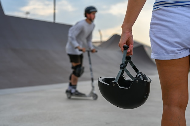 A woman holds a safety helmet after riding in an extreme park. the skate park, rollerdrome, quarter and half pipe ramps. extreme sport, youth urban culture for teen street activity.