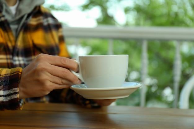 여자는 뜨거운 음료 한잔과 함께 접시를 보유 하 고, 클로즈업