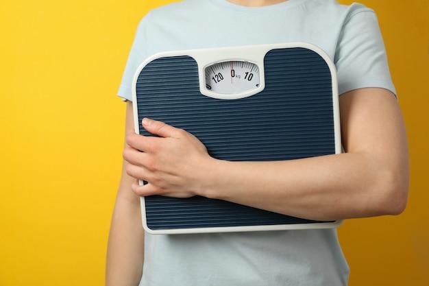 Женщина держит весы. потеря веса