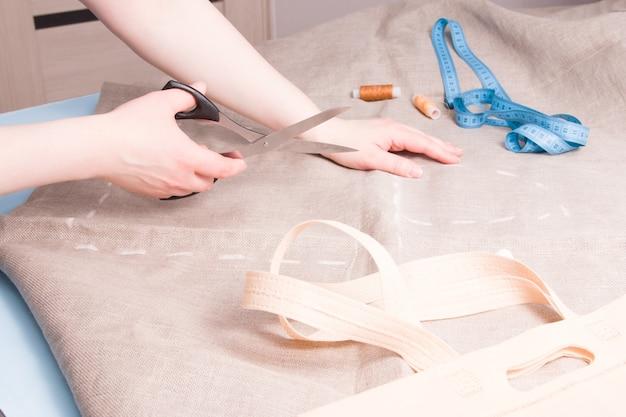Woman holds scissors to cut linen