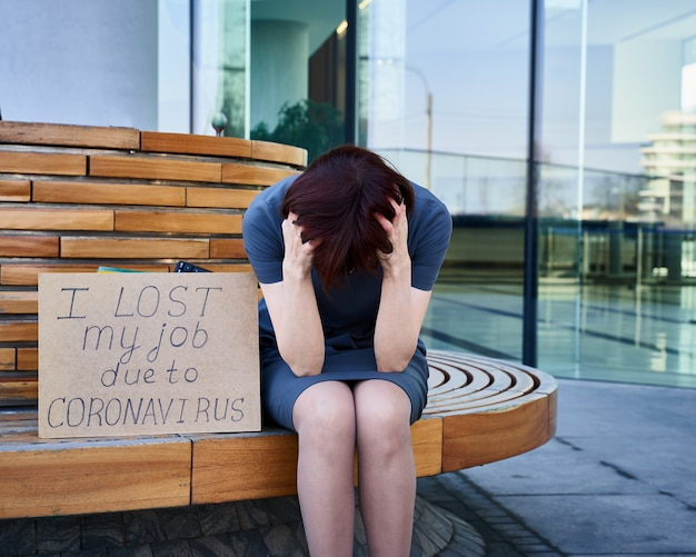Woman holds sign about job loss