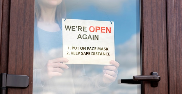 Woman holds sign behind the glass door of store