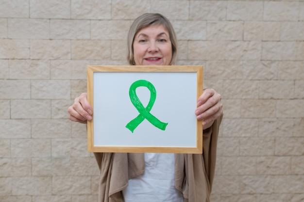 Woman holds a sign with a green ribbon for awareness and support of people living with disease.