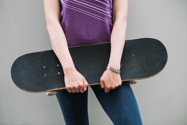 Женщина держит скейтборд