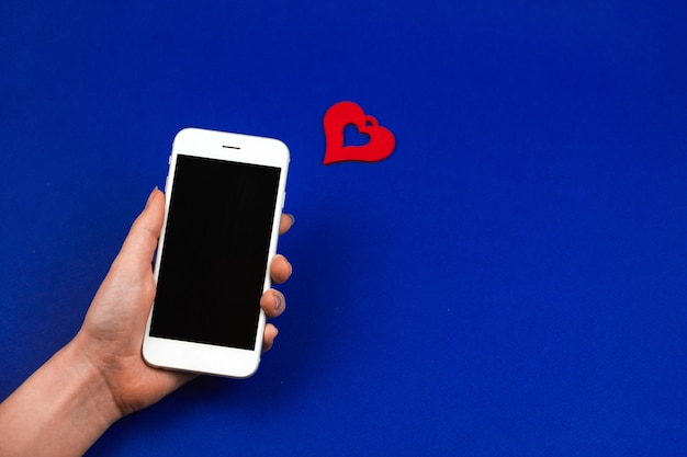 Woman holds smartphone with one love message notification, valentine's day concept on isolated blue background. high quality photo