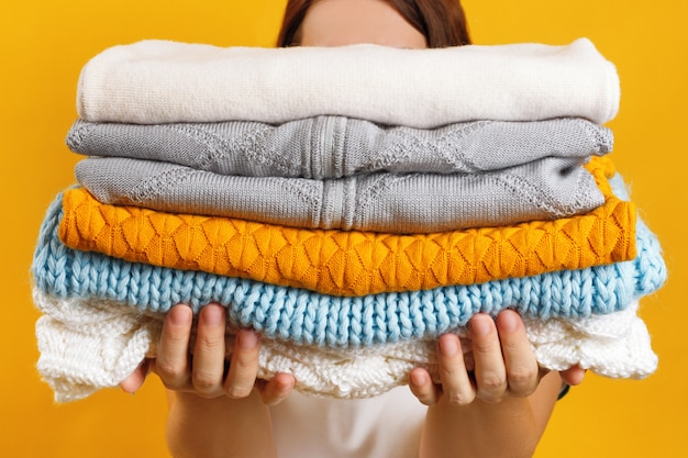 A woman holds a stack of warm knitted clothes
