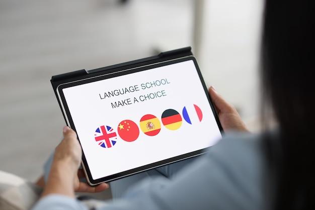 Женщина держит планшет и выбирает иностранный язык для изучения